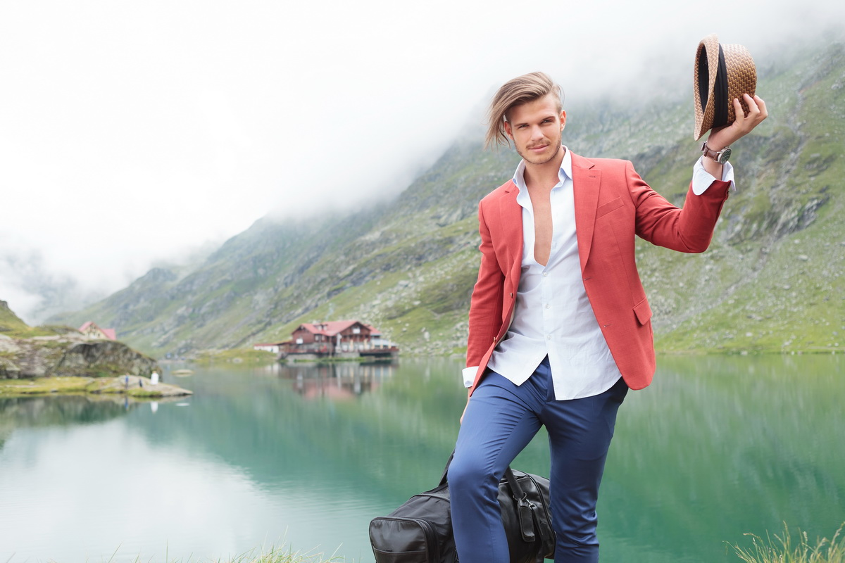 fashion man greets and welcomes you to a moutain lake with cabin
