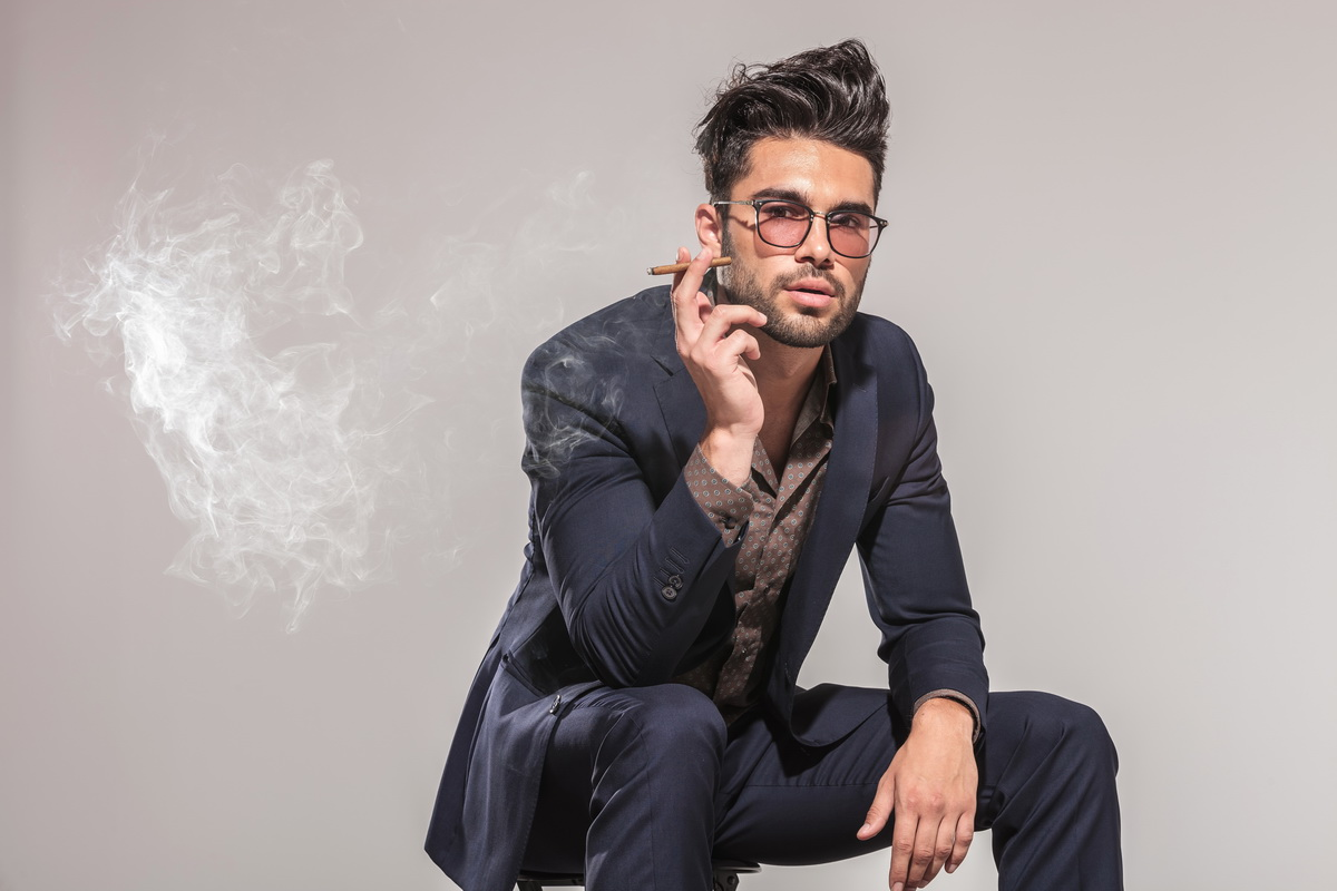 fashion man in suit sitting on chair and smoking , looking at the camera on grey studio background