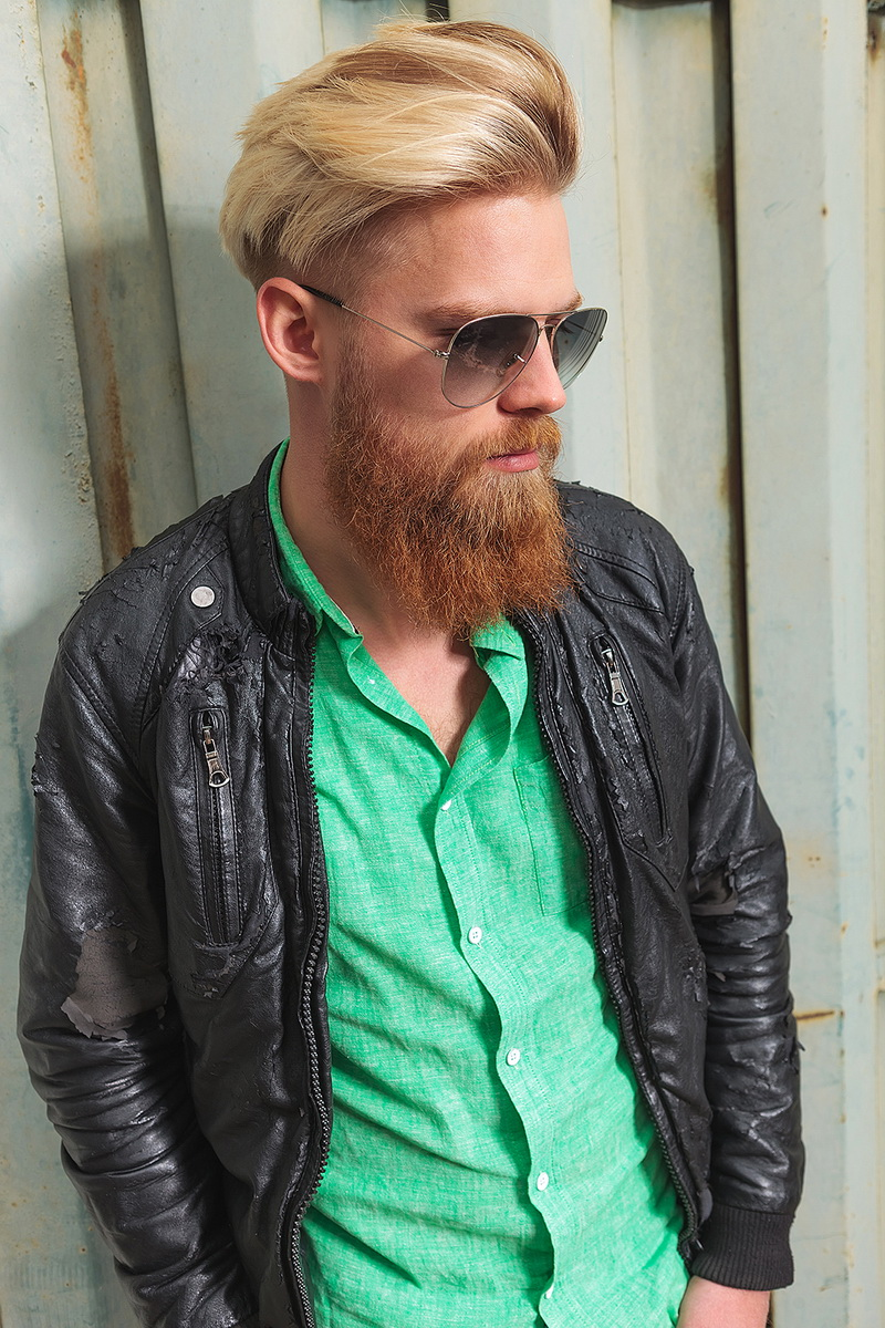 young casual redhead bearded man posing outdoor and looking down, away from the camera