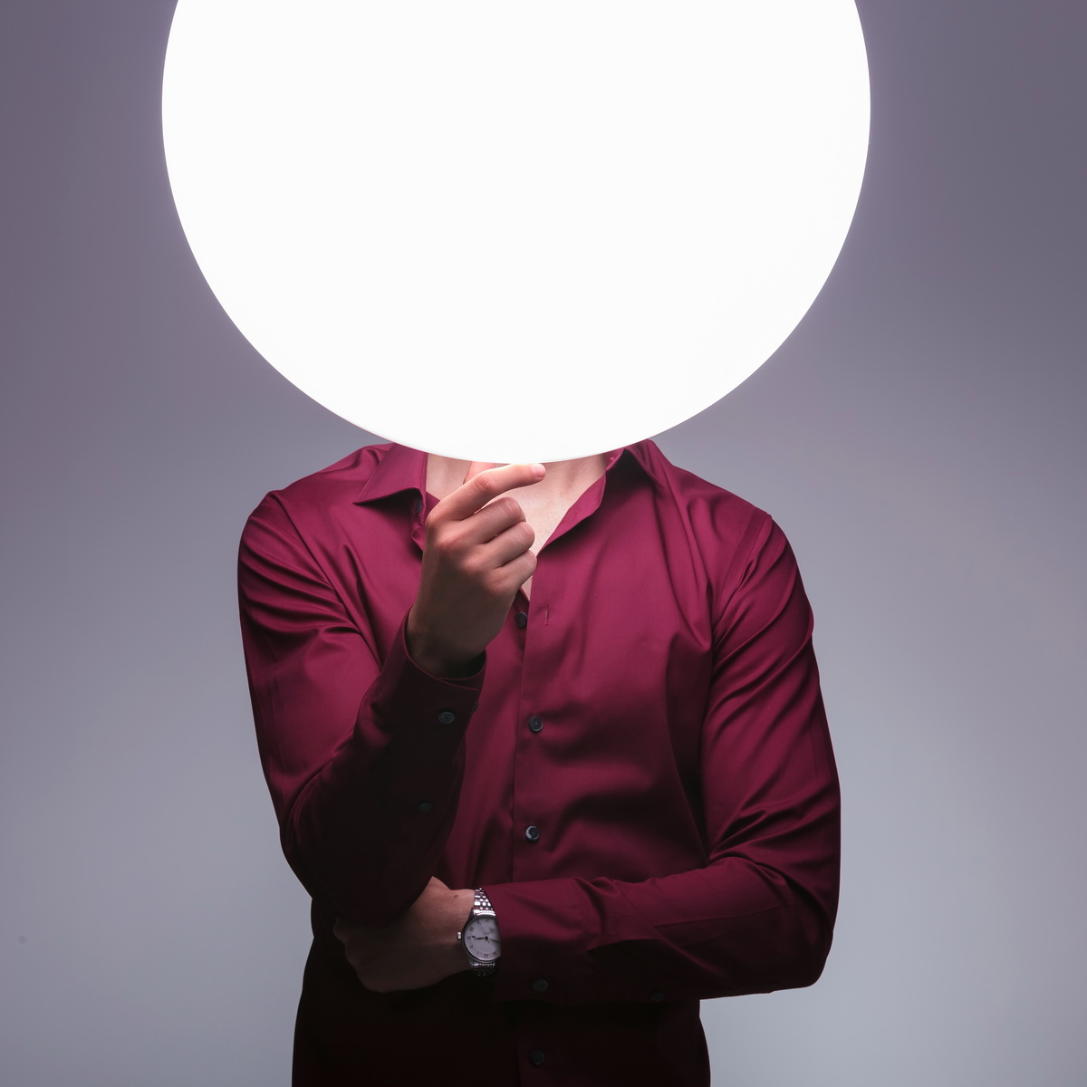 man with sphere of light as head is thinking on studio background