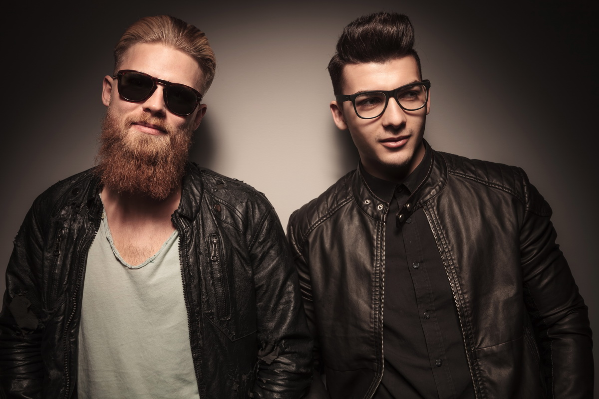 Two fashion male models in leather jacket posing against studio background, one with sunglasses and one looking away